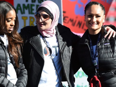 a black woman, a woman in a hijab, and a latina woman stand together on stage