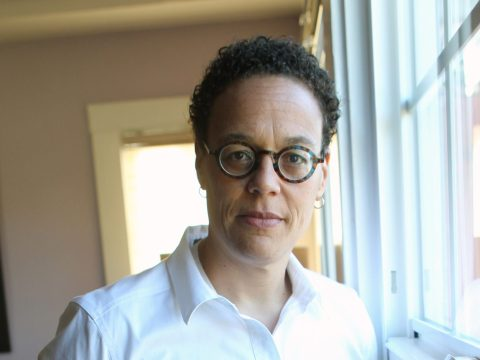 a black woman in glasses and a white shirt with a determined expression