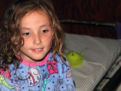 a kid with long hair and colorful PJs sits on a bunkbed
