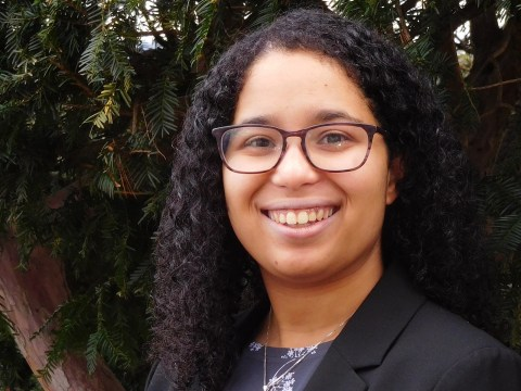 a young black woman smiling in glasses in front of a tree