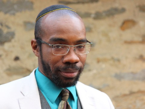 a bald black man in a suit and kipah, wearing glasses
