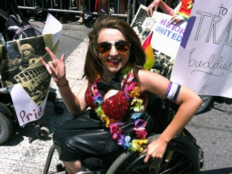 Cannington in a wheelchair wearing bright rainbow accoutrements, with parade-goers in the background
