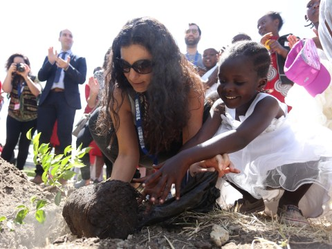 Ravit kneels on the ground with a young Kenyan girl, they are putting a small tree into the ground