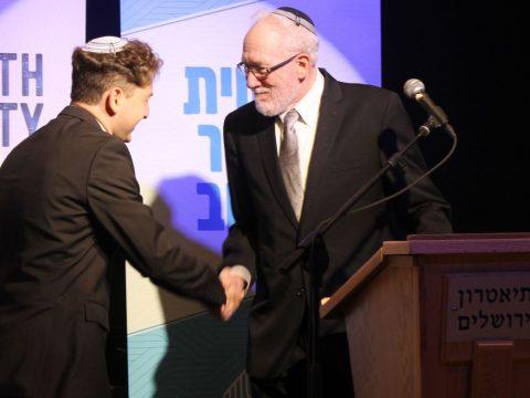 Newly ordained Rabbi Daniel Atwood is congratulated by Rabbi Daniel Landes at the Jerusalem Theater on May 26, 2019. (Photo/JTA-Sam Sokol)