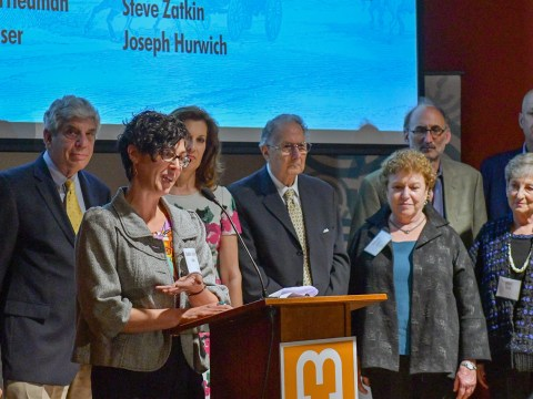Rabbi Adina Allen of Jewish Studio Project, a federation grantee, speaks, standing with past presidents of the Jewish Federation of the East Bay and Jewish Community Foundation at the 100th anniversary celebration of the federation, June 19, 2019. (Photo/Courtesy East Bay Federation)