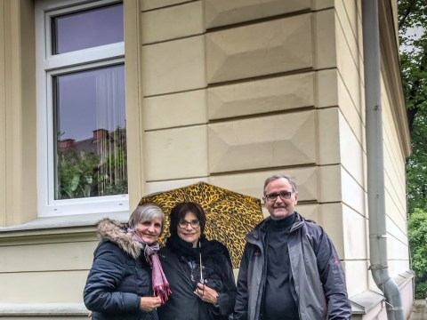 Sophie Weinzimmer (center) with guide Karl Ramsmaier (right) at Building 6 on Roosevelt Strasse, where Weinzimmer was born