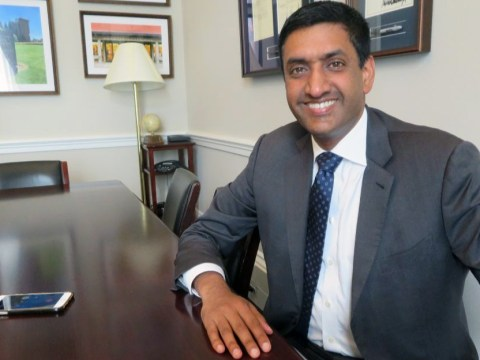 a smiling south asian man in a suit sits at a wooden table