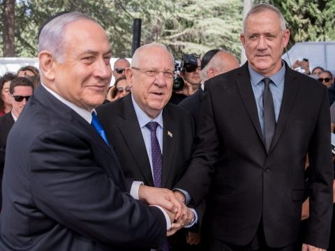 Netanyahu smiles while shaking the hand of a grimacing Gantz, Rivlin looks on