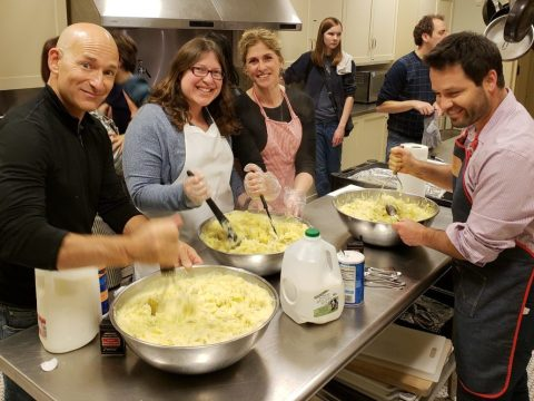 several people smile at the camera while mashing large bowls of potatoes in an industrial kitchen
