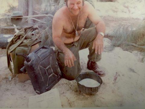 A shirtless Melamud kneels over his helmet, which is full of water