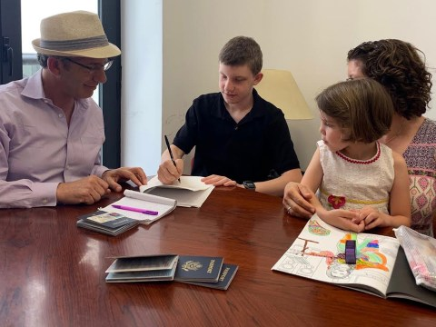 Dan Schifrin and Abby Friedman with children Lior and Elia signing citizenship documents in government office in Malaga, Spain.