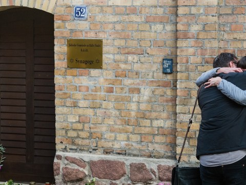 Mourners embrace in front of the entrance to the Halle synagogue in Germany a day after a deadly attack near there, Oct. 10, 2019. (JTA/Jens Schlueter/Getty Images)