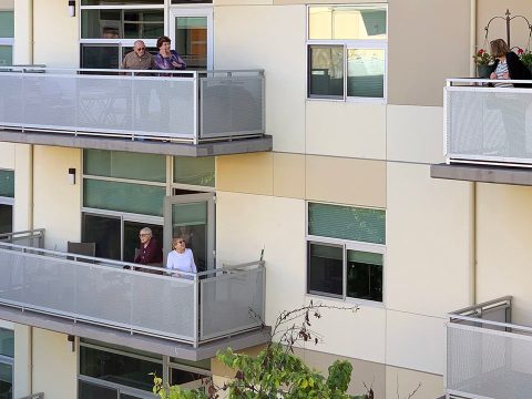 Quarantined residents of Moldaw Residences in Palo Alto greet each other from their balconies. (Photo/Frank Weiss)