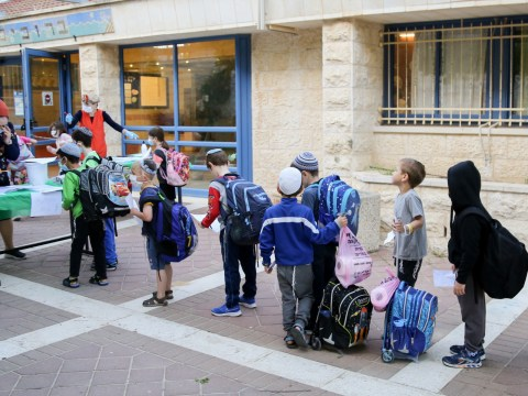 Israeli first- to third-graders social distance and bring doctor's notes at the entrance to their Jerusalem school, May 3, 2020. (Photo/JTA-Olivier Fitoussi-Flash90)