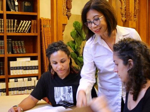 a latina woman stands talking to a pair of young women studying at a table