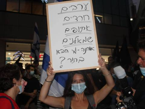 a woman in a mask holds up a white sign with hebrew text
