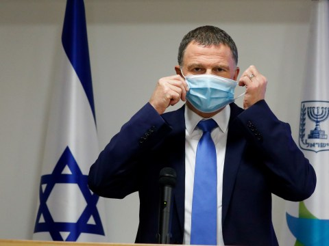 a man in a suit puts on a face mask. an israeli flag stands behind him.