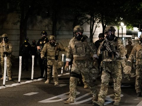 a dozen men in camo and gas masks march down a street