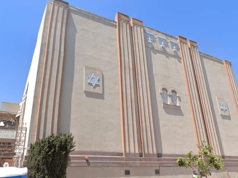 facade of a beige building with art deco lines, adorned with six-pointed stars and the ten commandments tablets