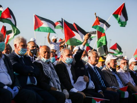rows of mostly older men sit in chairs, while others wave Palestinian flags behind them