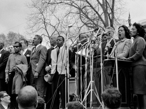 black and white photo of several black people standing at microphones on a raised platform