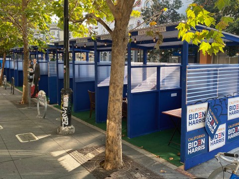 a series of covered blue wooden booths with Biden-Harris posters on them line a sidewalk