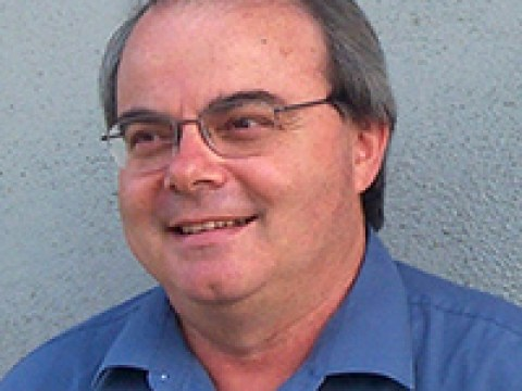 headshot of a balding middle aged white man in glasses and a blue shirt