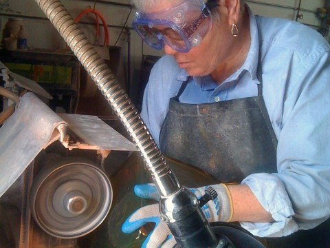 "Carol Roseman grinding and polishing a glass box for her sculpture, ""Fragile,"" in 2012. (Photo/Courtesy Carol Roseman)"