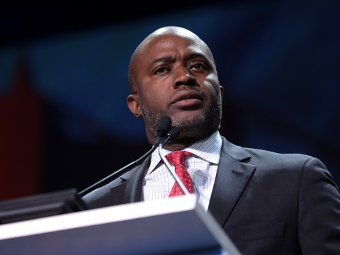 a middle aged black man in a suit speaks at a podium