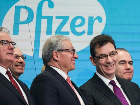 Pfizer CEO Albert Bourla (right, in purple tie) waits to ring the closing bell at the New York Stock Exchange, Jan. 17, 2019. (Photo/JTA-Drew Angerer-Getty Images)