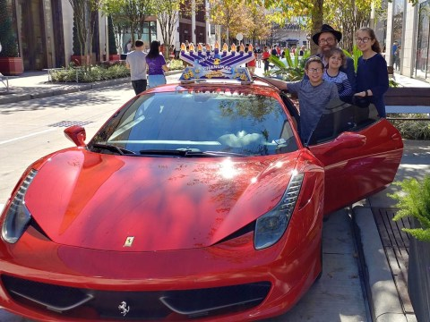 Houston Chabad Rabbi Chaim Lazaroff with his family and a menorah on a Ferrari that toured the city in 2018. (Photo/JTA-Chabad of Uptown)