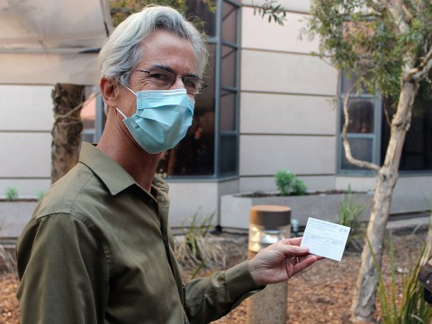 "Dr. Stephen Hall smiles with his ""Covid-19 Vaccination Record Card"" after receiving the Pfizer-BioNTech Covid-19 vaccine at San Francisco Campus for Jewish Living, Dec. 21, 2020. (Photo/Gabriel Greschler)"