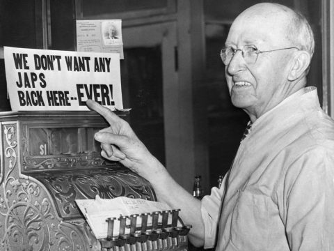 During the internment of Japanese Americans, barber G.S. Hante points proudly to his bigoted sign. (Photo/JTA-Bettman-Getty Images)