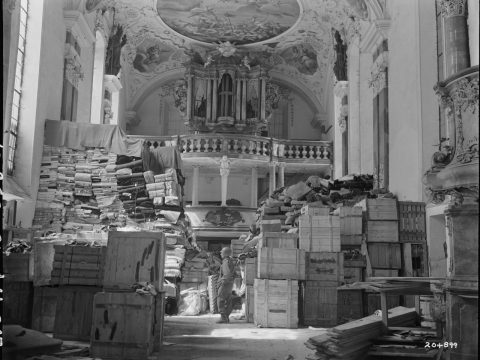 An merican soldier inspects German loot stored in a church in Elligen, Germany, April 24, 1945. (Photo/National Archives)