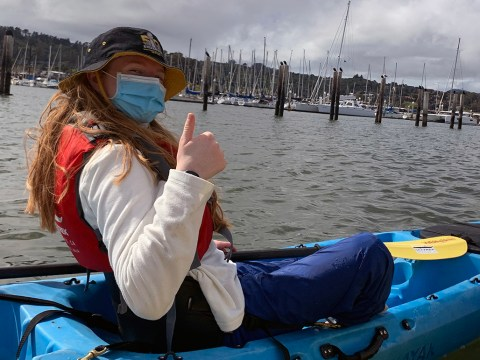 a young woman with blond hair and wearing a facemask smiles and makes a thumbs up while sitting in a kayak on the water.