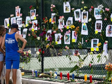 Cheri Fine, left, and Mark (no last name provided) visit a makeshift memorial at the site of the collapsed building with photos of the missing in Surfside, Florida, June 26, 2021. (Photo/JTA-Andrea Sarcos-AFP via Getty Images)