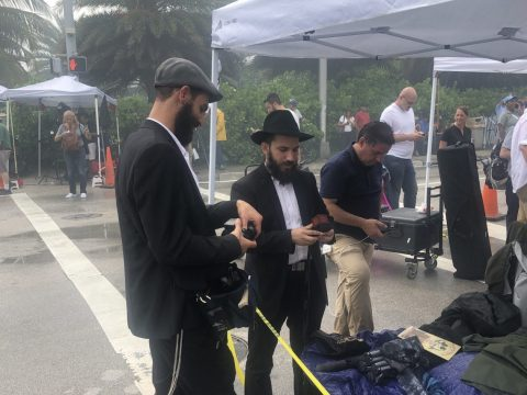 Uriel Gabbay (left) and Dovi Alperovich seek Jewish males to fulfill the mitzvah of putting on tefillin a block away from the collapsed building, June 25, 2021. (Photo/JTA-Ron Kampeas)