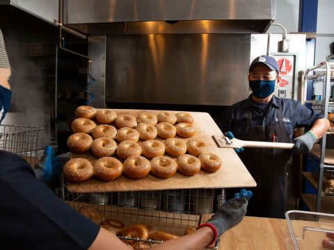 two masked bakers handle a large wooden pallet of sesame bagels
