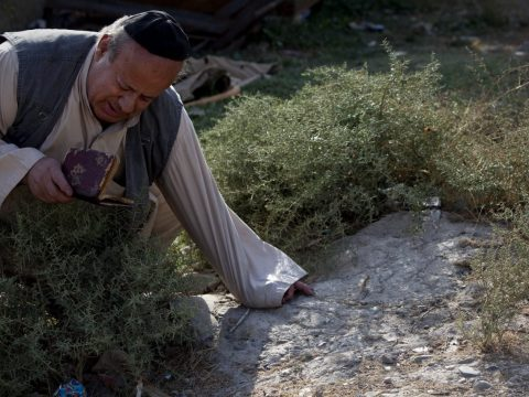 Zebulon Simantov touches the grave of his family members in Kabul, Afghanistan in 2009. (Photo/JTA-Paula Bronstein/Getty Images)