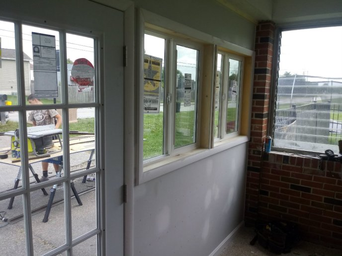 The finished interior wall with double windows and french doors with custom casing and trim
