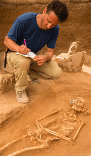 Cemetery excavation supervisor Adam Aja examines a 10th-9th century BC burial during the excavation of the Philistine cemetery by the Leon Levy Expedition to Ashkelon ©Tsafrir Abayov/Leon Levy Expedition