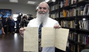 Dr. Roni Grosz, curator of the Hebrew University's Albert Einstein Archives, holds a page from Einstein's General Theory of Relativity. Photo: Dov Smith for The Hebrew University of Jerusalem