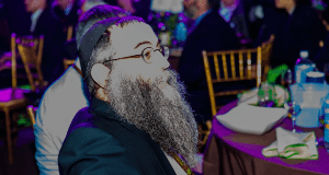 Rabbi Mendy Groner, of Melbourne Australia, seated among his colleagues at a banquet at the Brooklyn Marine Terminal Pier 8 in the Brooklyn borough of New York on November 27, 2016. He is among 5,600 rabbis and guests from 90 countries in New York for the International Conference of Chabad-Lubavitch Emissaries, an annual event aimed at reviving Jewish awareness and practice around the world. This year's conference carries an added significance as the North American Jewish community marks 75 years since Rabbi Menachem M. Schneerson, of blessed memory, the movement's leader, arrived on U.S. shores from war-torn Europe in 1941. Credit: Eliyahu Parypa / Chabad.org