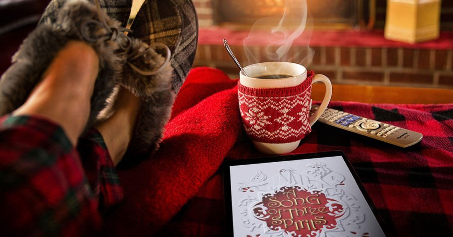 A man kicking up his feet with a cozy holiday mug and an e-reader loaded up with A Song of Three Spirits