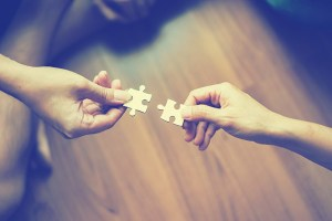 Hands fitting puzzle pieces together