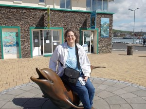 My sister sitting on a dolphin sculpture.