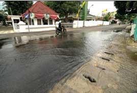 BANJIR: Air meluber dari selokan di depan gerbangkantor pemkab di Jalan Borobudur, Banyuwangi.