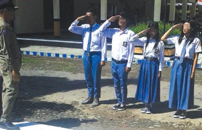 Pelajar-yang-terjaring-razia-Satpol-PP-Muncar-diberi-sanksi-berupa-hormat-pada-bendera-sambil-menyanyikan-lagu-Indonesia-Raya-kemarin.