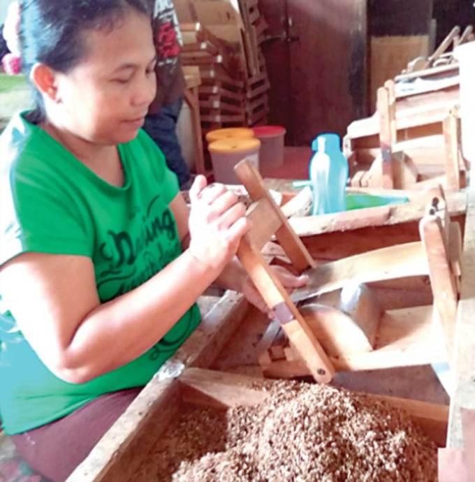 Seorang-buruh-sedang-bekerja-memproduoksi-rokok-di-sebuah-home-industry-di-Jalan-Serayu-Nomor-62,-Kelurahm-Panderejo,-Banyuwangi,-kemarin.