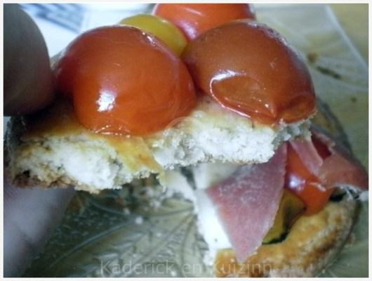 Recette des Tartelettes tomates cerises bio, mozzarella et jambon de pays pour une entrée servi avec une feuille de basilic